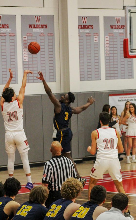 During+the+Highland+Park+vs.+Woodrow+Wilson+varsity+basketball+game+last+Tuesday%2C+Prince+Dorbah+%283%29+went+up+to+block+a+three+point+shot+from+number+24+on+the+opposing+team.+