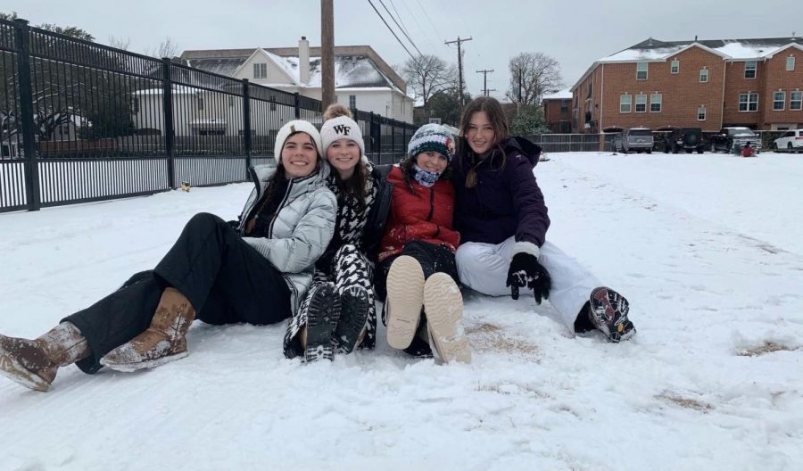 Seniors Isabel Applewhite, Hilary Hansford, Sarah Rogers and Katie Arnold sit together while watching their friends sled behind a car. Because there was no school for the week, the students made the best of it and spent quality time with friends.
