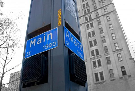 A street sign marks the intersection of Main  and Akard Street in Downtown Dallas. In 1910, this was the location where an angry mob lynched a Black man named Allen Brooks on a structure called Elk