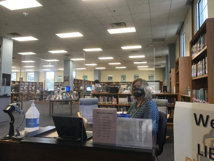 Librarian+Bonny+Urschel+patiently+waits+for+students+to+sign+in+as+they+come+through+the+library.+Students+must+sign+in+immediately+upon+entering+the+library.