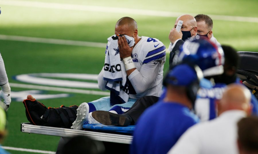 Dallas Cowboys quarterback Dak Prescott cries after being taken off the field alongside medical staff.  Soon after Dak left the game, second string quarterback Andy Dalton stepped in for the remaining game time.