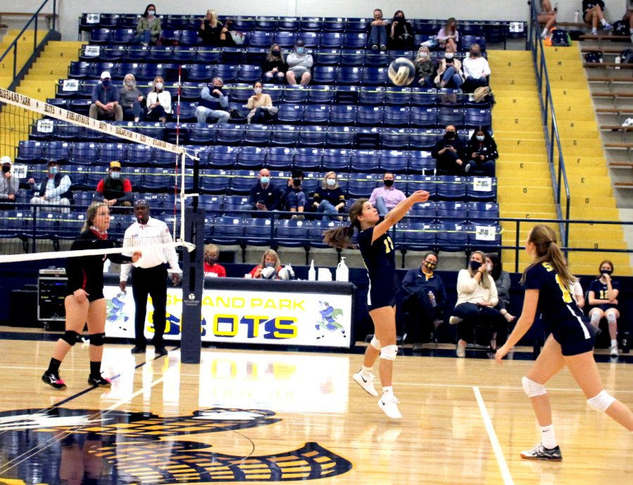 Setter Sophie Sutton (#13) is getting ready to hit the ball back to the other side of the net, her teammate middle blocker Ava Iredale (#14) is there for backup. The team saved the ball and ended up scoring the next point.