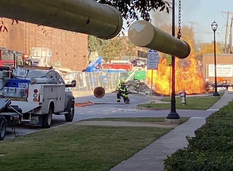 After a gas line explosion, a fire burns in the street near the Westchester entrance of the parking garage. The fire sent two Atmos workers to Parkland Hospital, and it occurred a day after students and staff were evacuated from the building.