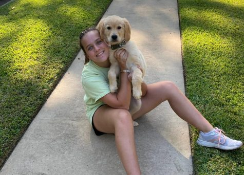 """Sophomore Emily Bailey poses for a picture with her new puppy, Buck. Her family recently adopted Buck during the quarantine. """"We all take care of him,"""" Bailey says."""
