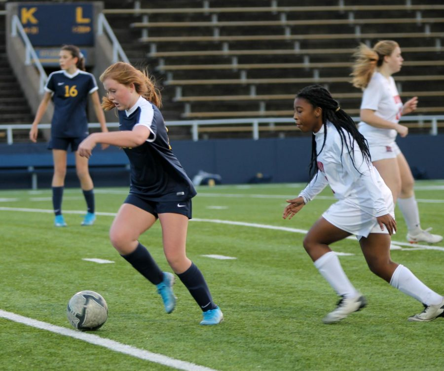 Freshman Lauren Ridgway runs with the ball, Mckinney Boyd's players in hot pursuit. She played midfield.
