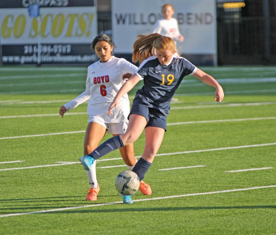 Freshman Lauren Ridgway, who plays midfield, clashes with a Mckinney Boyd player to get the ball to her teammates. Her teammate Molly Saunders scored a corner kick goal to tie the game.