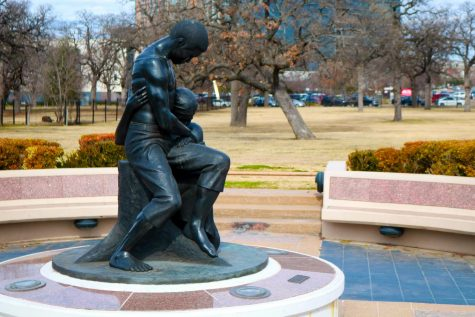 A statue depicting two Black former slaves embracing, one with a scarred back from whips, sits at the middle of the Freedman