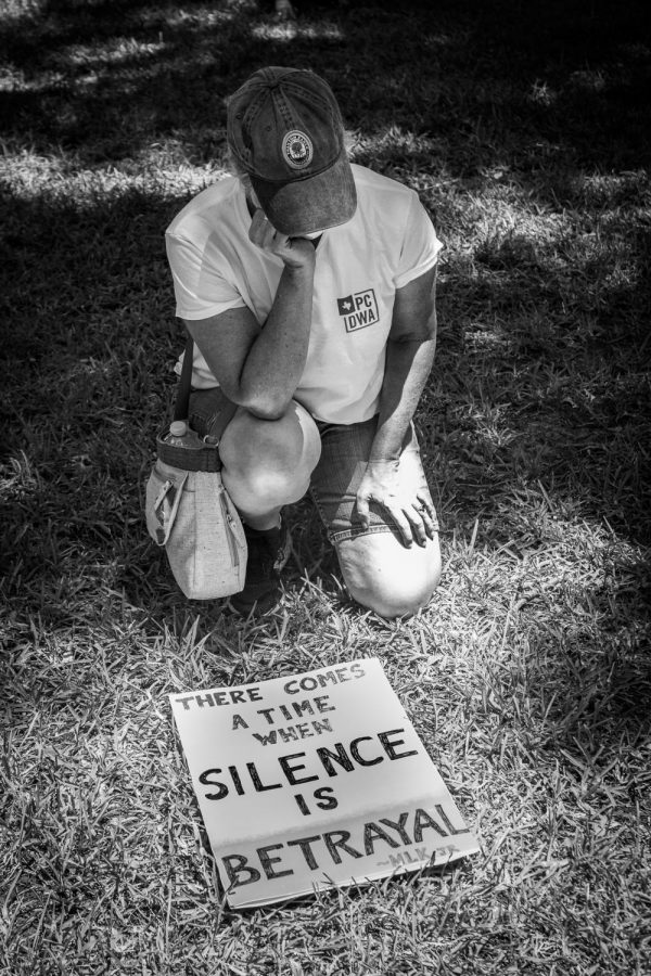 A high school parent kneels with her sign during an 8 minute moment of silence in honor of George Floyd. When Floyd's death sparked nationwide protests in honor of the Black Lives Matter movement, Park Cities residents held local events. Shortly after, a group of students crafted a video titled
