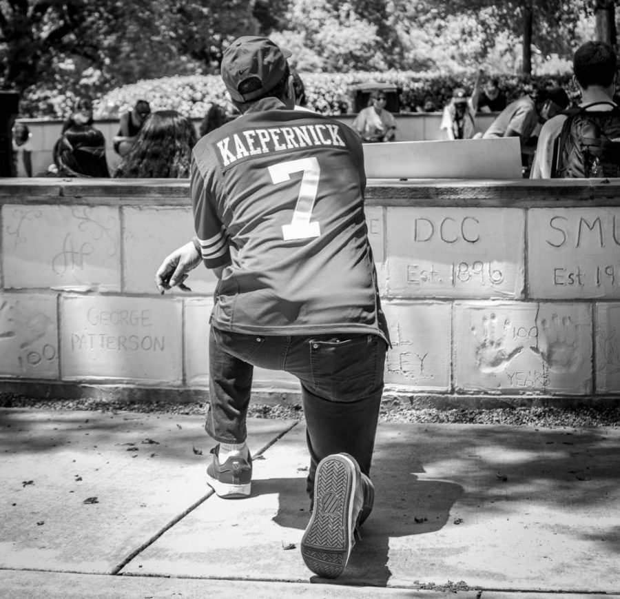 Highland Park resident kneels during the eight-minute moment of silence in honor of George Floyd while wearing a Colin Kaepernick jersey. Kaepernick is an American civil rights activist and football quarterback known for kneeling during the U.S. anthem in protest of police brutality and racial inequality.