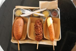 The Pickle (left), the Bacon (middle), and the Corn Dog Queen (right) sit on the tray with multiple containers of mustard and ketchup. The Pickle contained a juicy pickle with the meat inside the pickle. The Bacon contained a pork sausage infused with jalapeno and cheddar cheese. The Corn Dog Queen was very similar to the Classic, but the only difference was the piece of 24K gold on the tip.