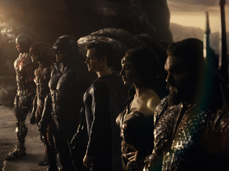 Ray Fisher (Cyborg), Ezra Miller (The Flash), Ben Affleck (Batman), Henry Cavill (Superman), Gal Gadot (Diana Prince), and Jason Momoa (Aquaman) all pose for group shot looking in the distance.