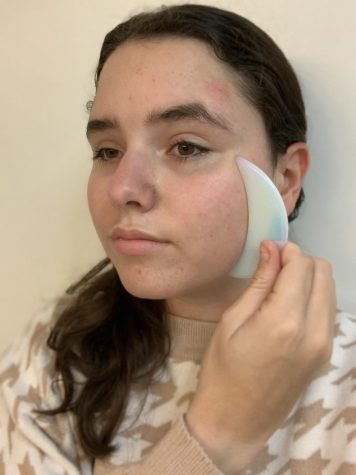 Freshman Isabella Navarro uses the Gua Sha. Navarro planned on trying the tool for a few days to see if results are in store.