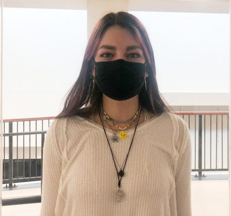 """Sophomore Alessia Cordray poses for a picture showing off her necklaces. Most notably a sunshine charm on a beaded, an evil eye (a greek charm to ward off against evil spirits), and two crystals on a rope necklace. """"Im wearing clear quartz and moldavite,"""" Cordray said."""