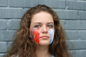 Audrey Schedler, an ally of the queer community, poses with the gay and trans flag colors on her cheeks.