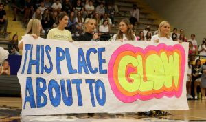 While they announce the theme for the Hilites dance, seniors Grace Newhouse, Katelyn Turco, Piper Soetenga, Sterling Williams and Meg Lochausen hold up a banner. The announced theme for the dance was This Place About To Glow, which calls for neon colors in students outfits.